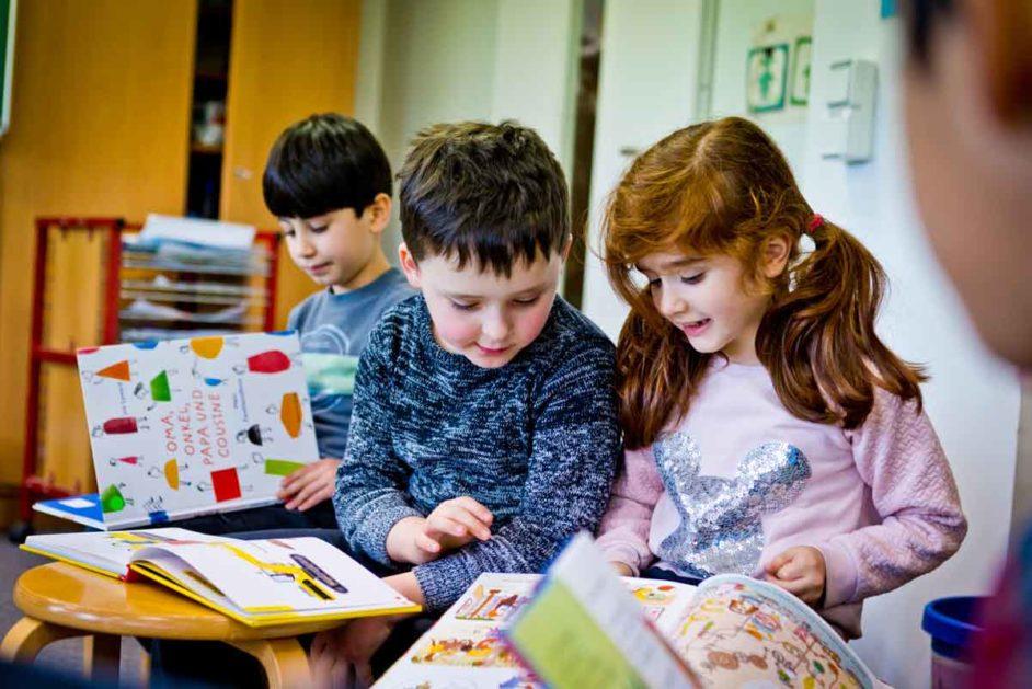 Kinder schauen Bücher an.