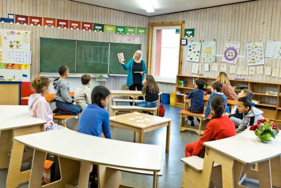 Grundschulkinder sitzen im Kreis im Klassenraum.