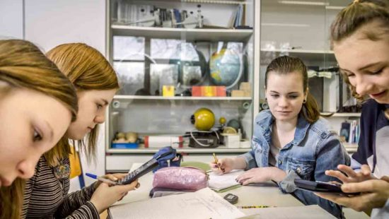 Schülerinnen arbeiten am Gruppentisch gemeinsam an einer Aufgabe