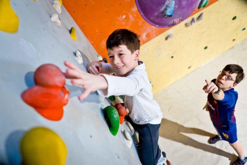 Ein Junge klettert an der Kletterwand