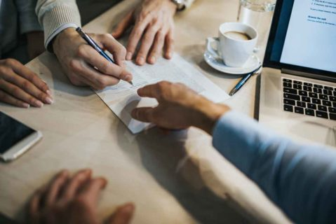 Hände von verschiedenen Personen übergeben Unterlagen am Schreibtisch