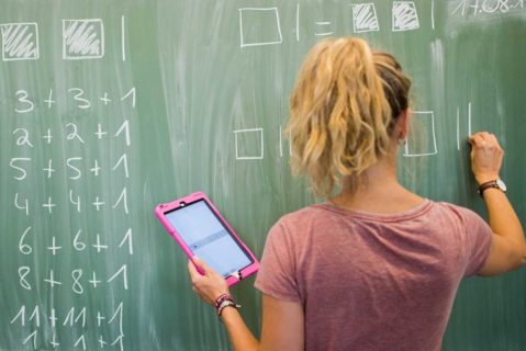 Eine Lehrerin schreibt Zahlen an die Tafel und hält dabei ein Tablet in der Hand.