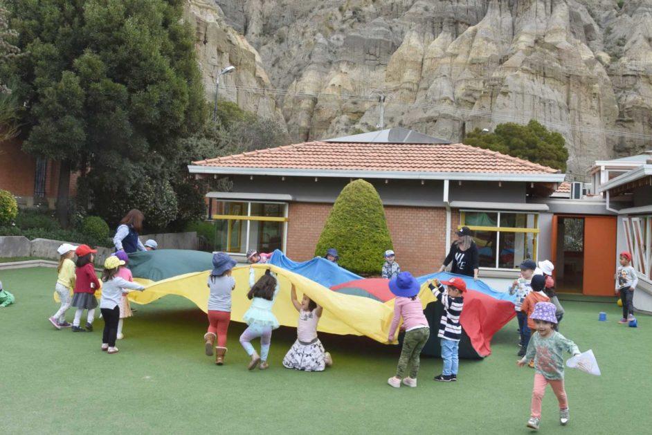 Die Kinder spielen auf dem Campus mit faszinierender Kulisse.