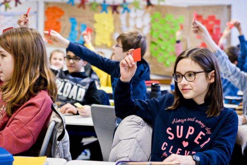Schülerinnen und Schüler stimmen demokratisch in der Klassengemeinschaft statt.