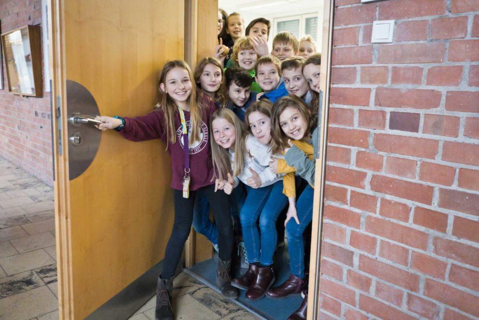 Eine Klasse lässt sich in der Tür ihres Raumes fotografieren.