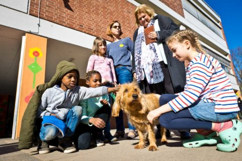 Schülerinnen und Schüler und eine Lehrerin lassen sich mit der Schulhündin fotografieren.