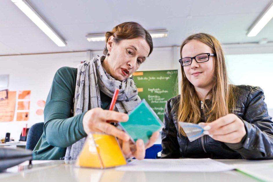 Eine Pädagogin und eine Schülerin betrachten gemeinsam eine geometrische Form.
