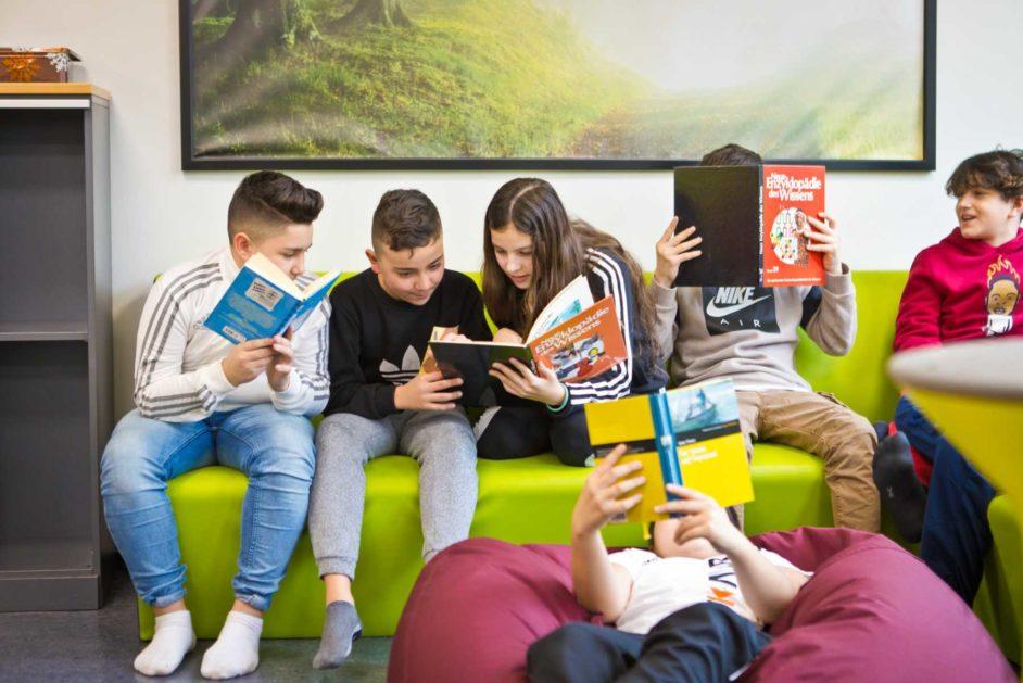 Jugendliche lesen Bücher aus der Schulbibliothek.