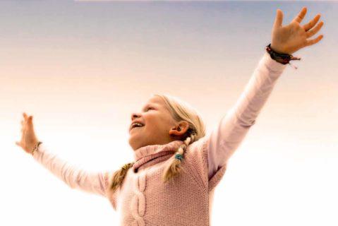 Kind lacht mit ausgebreiteten Armen