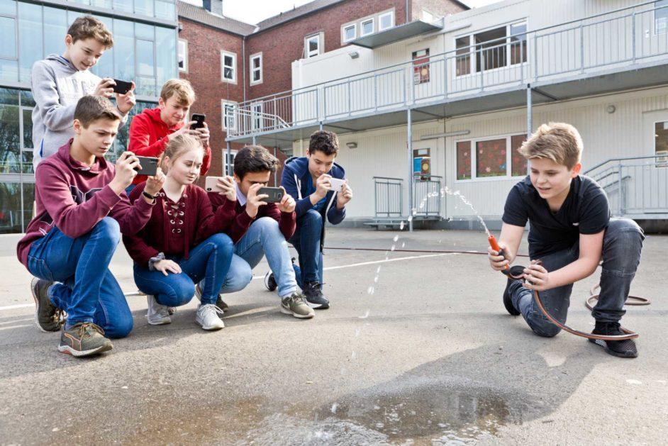Ein Schüler versucht einen Wasserstrahl mit einer bestimmten Neigung zu erzeugen.