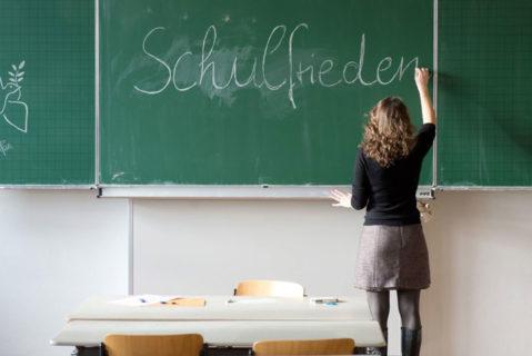"""Lehrerin schreibt """"Schulfrieden"""" an dei tafel"""