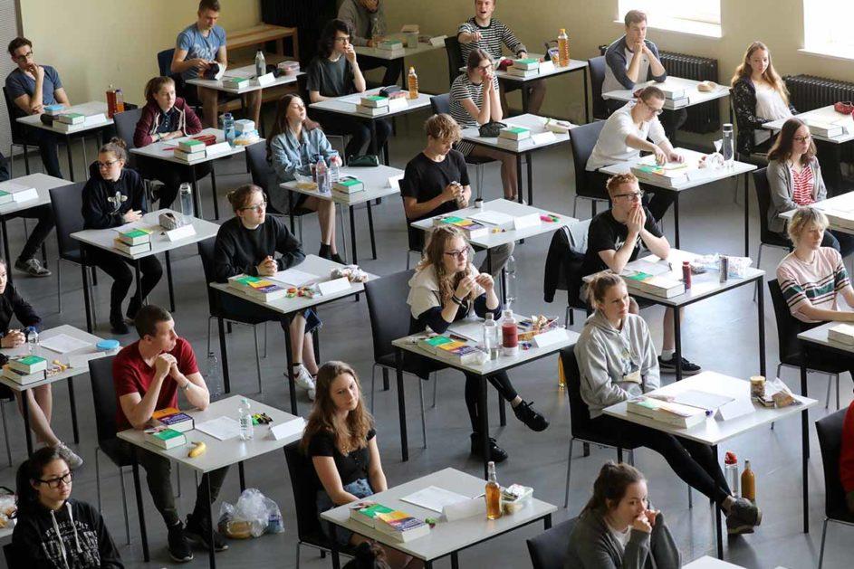 Abiturienten sitzen bei der Prüfung an einzelnen Tischen
