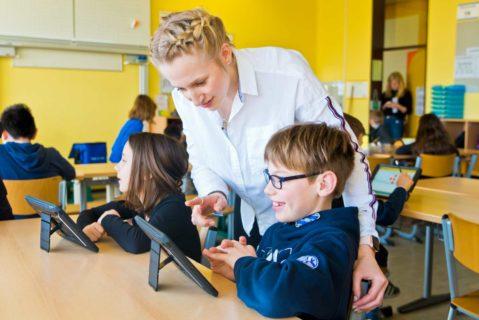 Eine Lehrerin widmet sich einem Schüler, während dieser eine Aufgabe am Tablet bearbeitet.