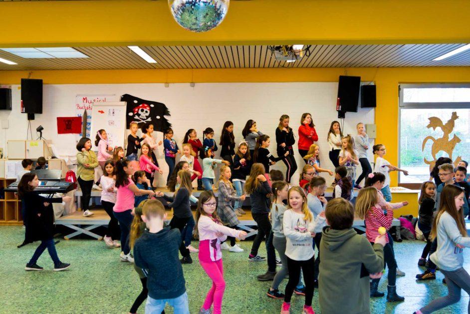 Die Kinder tanzen gemeinsam in der Aula der Gebürder-Grimm-Schule.