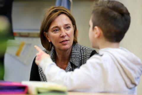 Yvonne Gebauer (l, FDP), Bildungsministerin in Nordrhein-Westfalen, spricht mit einem Schüler in der Grundschule.