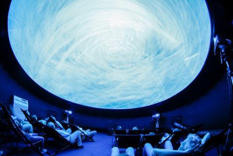 Schüler liegen in Liegestühlen und bestauenen einen künstlichen Mond