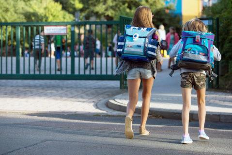 Schülerinnen überqueren eine Straße