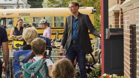 Schulleiter mit Kindern vor Eingang der Auslandsschule