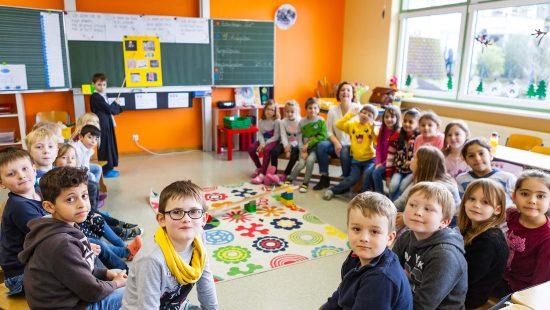 Kinder der Grundschule in Mengerskirchen sitzen zusammen in einem Stuhlkreis.