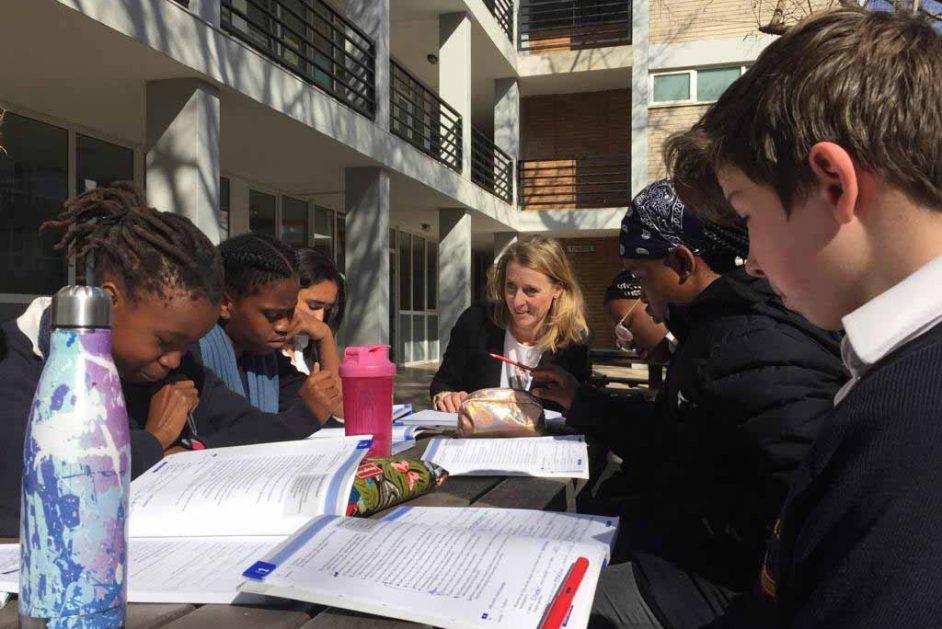 Lehrerin und Schüler vor dem Schulgebäude mit Heften