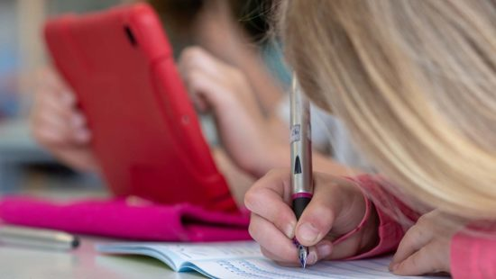 Schüler schreiben mit der Hand und mit dem Tablet