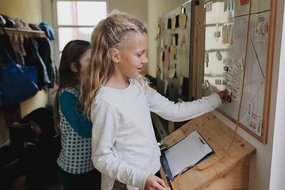 Ein Mädchen steht an einer Magnettafel