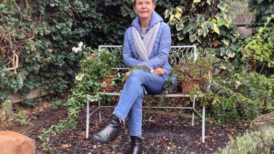 Frau im Garten auf Bank