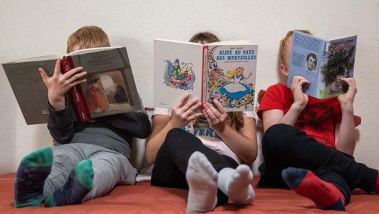 Drei Kinder lesen jeweils ein englisches, ein französisches und ein deutsches Buch.