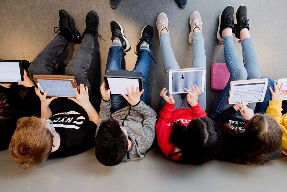 Schülerinnen und Schüler sitzen mit iPads im Mathe-Unterricht am Boden