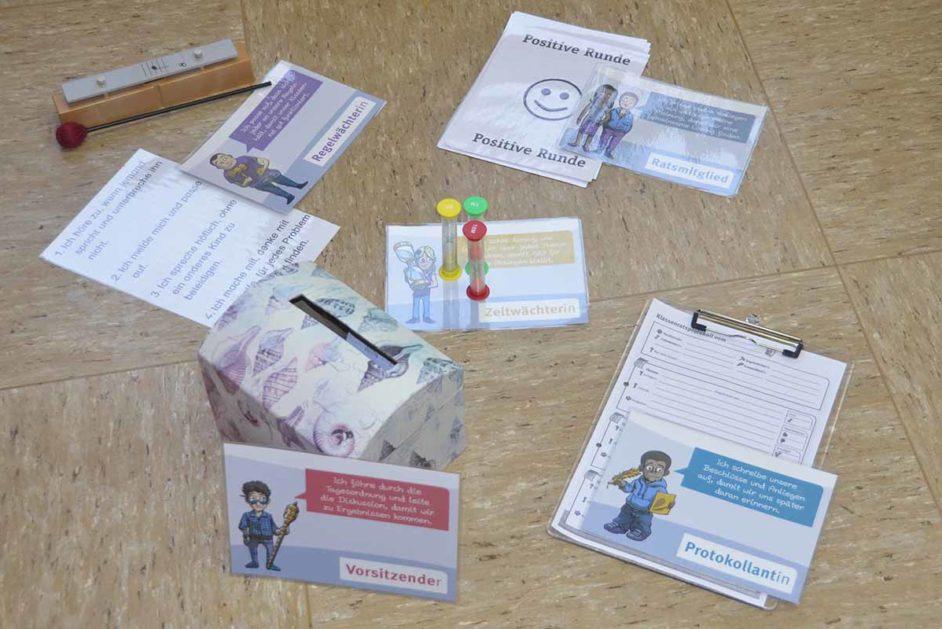 Karten, Sanduhr, Zettel für den Klassenrat auf dem Boden
