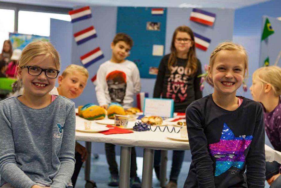 """Willkommenskultur in der Schule: Kinder mit französischen Fahnen im """"Ländercafé"""""""