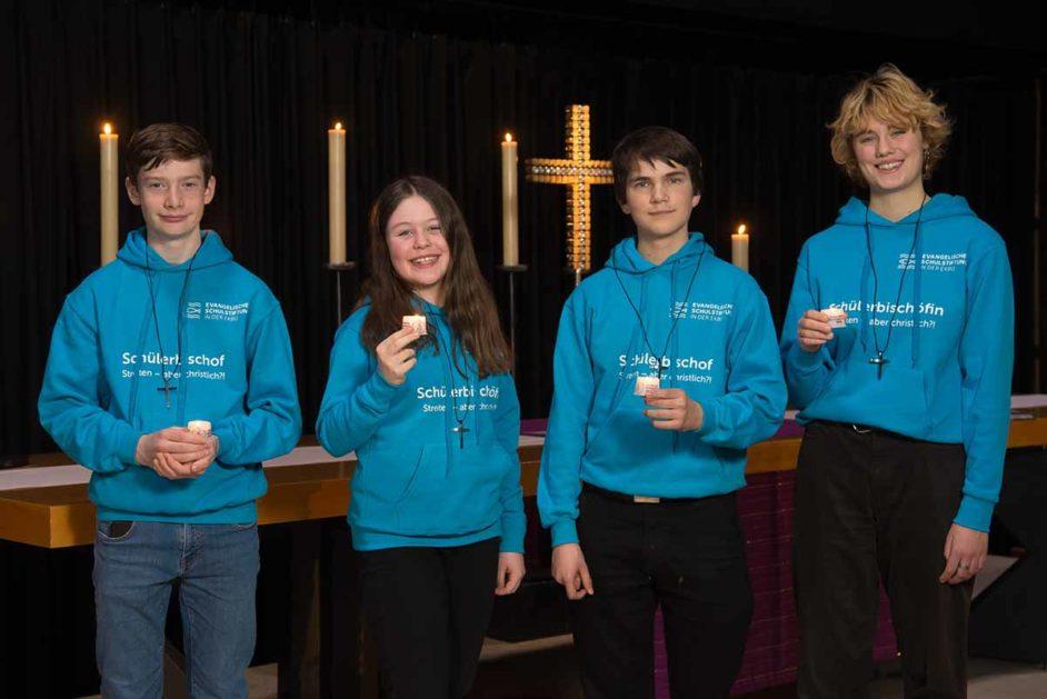 Schülerbischöfe mit Kerze in Kirche
