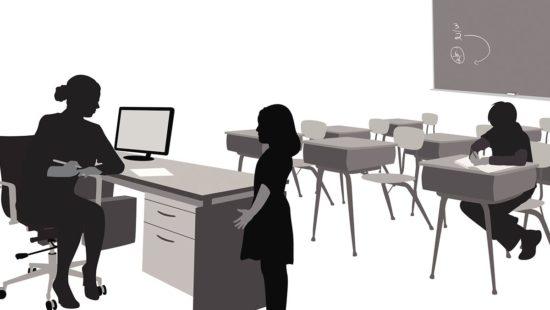 Mädchen steht vor Lehrerin