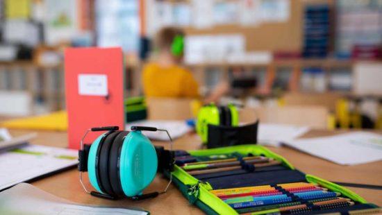Auf dem Tisch liegt ein Gehörschutz neben Heft und Federmappe