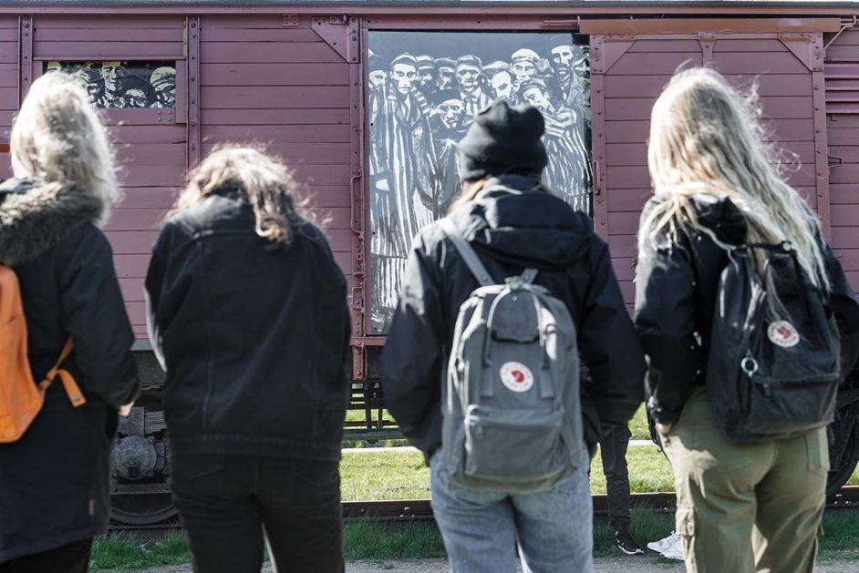 Schülerinnen einer 9. Klasse betrachten auf einem Rundgang einen historischen Reichsbahnwaggon, der symbolisch für den ehemaligen Lagerbahnhof des Konzentrationslagers Neuengamme steht.