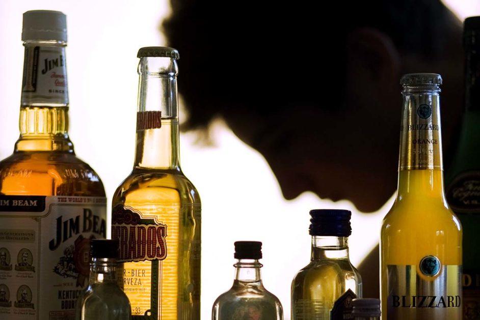 Ein Jugendlicher sitzt hinter Flaschen mit Alkohol. Bei Alkohol ist Deutschland ein Hochkonsumland und auch in Nordrhein-Westfalen trinken Experten zufolge viele Menschen in problematischen Mengen. Allein in der Altersgruppe der 18- bis 64-Jährigen nehmen bundesweit rund 7,8 Millionen Menschen in riskantem Mafle Alkohol zu sich, wie die Deutschen Hauptstelle für Suchtfragen mitteilte.
