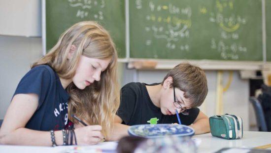 Ein Mädchen und ein Junge sitzen über einer Matheaufgabe.