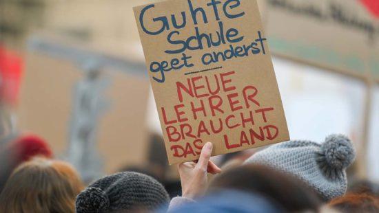 """Bei einer Demonstration wird ein Schild mit der Aufschrift """"Guhte Schule geet anderst. Neue Lehrer braucht das Land"""" hochgehalten."""