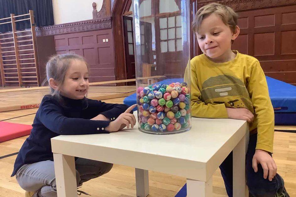 Zwei Kinder vor einem Glas mit Flummis