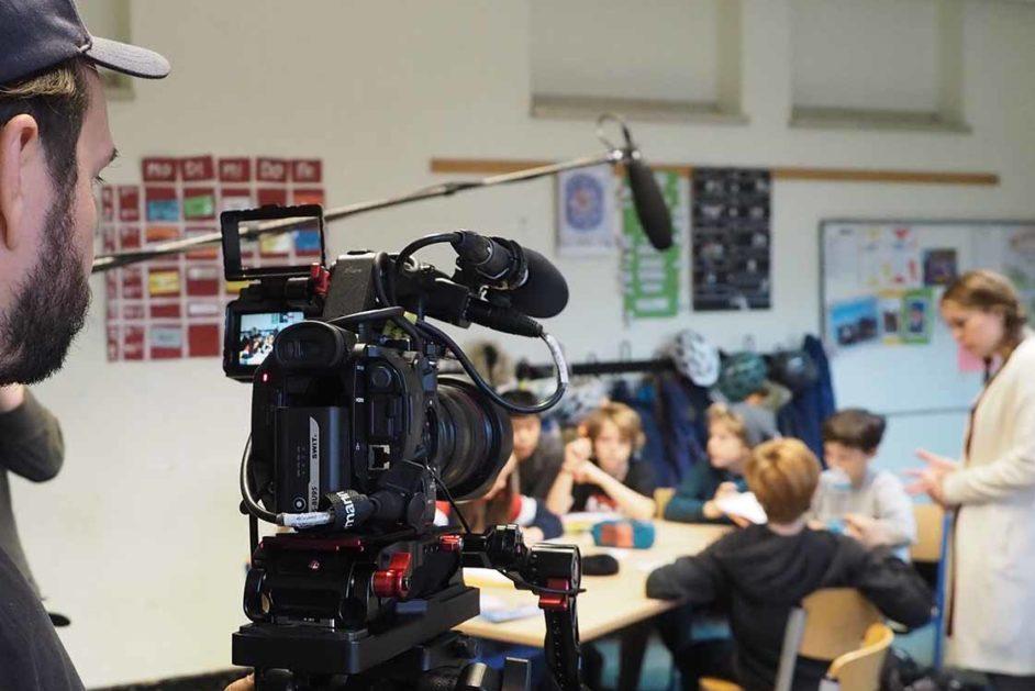 Kamera, Schüler an einem Tisch mit Lehrerin