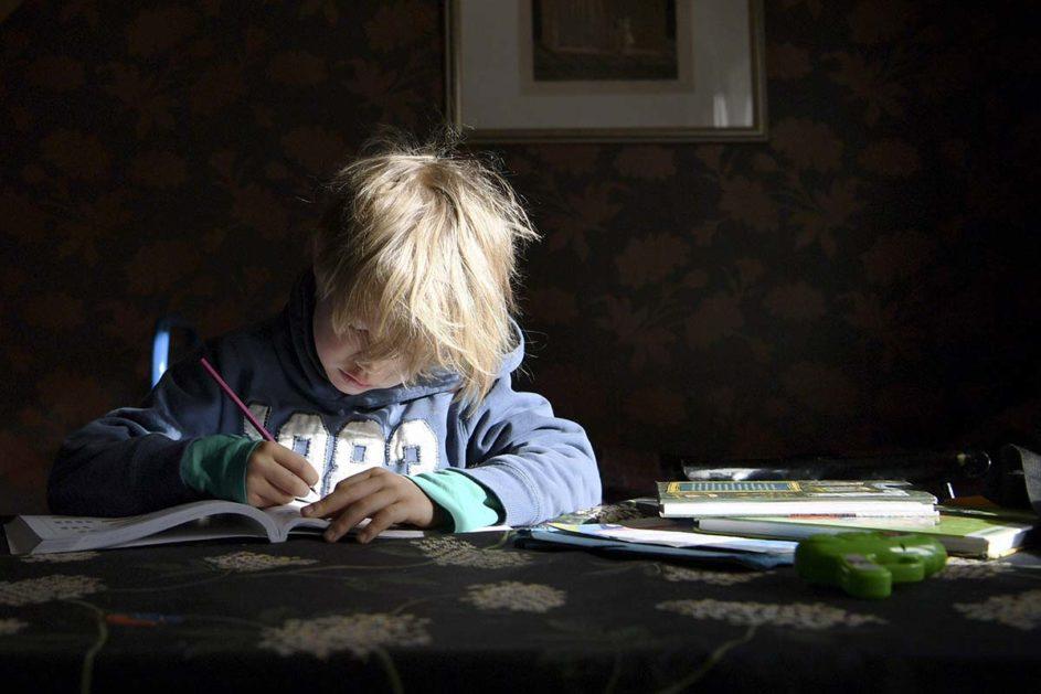 Junge sitzt in der Zeit der Schulschließung zu Hause am Tisch und lernt