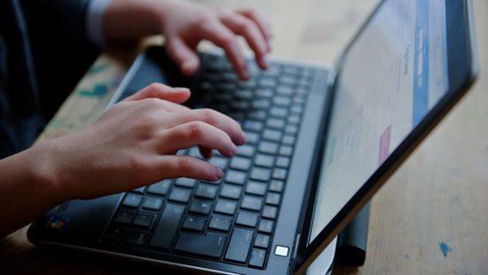Hände auf Tastatur Laptop