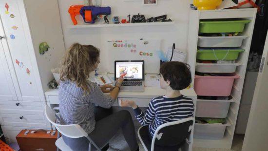 Mutter hilft ihrem Sohn im Kinderzimmer beim Lernen