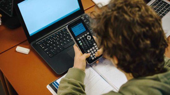 Junge mit Taschenrechner vor Computer