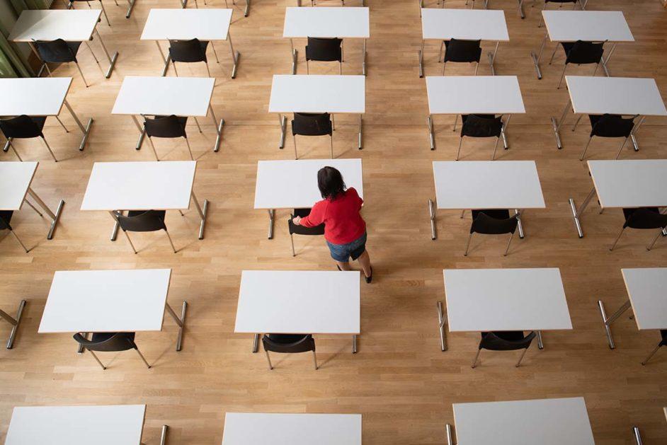 Eine Frau bereit in der Aula im Sorbischen Gymnasium Bautzen Tische und Stühle für die bevorstehenden Abschlussprüfungen vor.