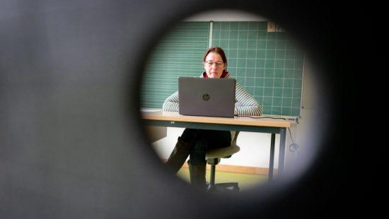 Lehrerin sitzt während der Corona-Krise vor Laptop im leeren Klassenraum
