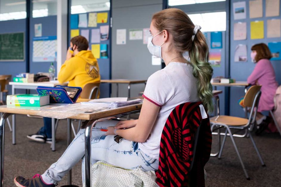 Schüler sitzen mit Abstand und Mundschutz im Klassenraum