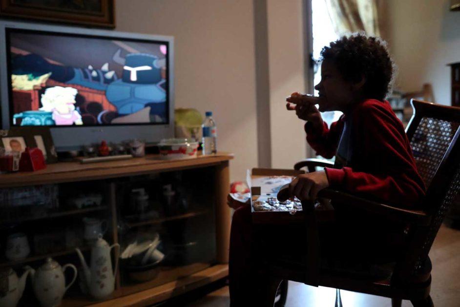 Ein Junge schaut Fernsehen und ist dabei eine Pizza