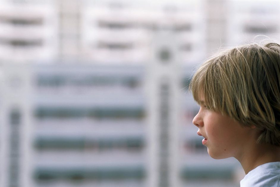 Kind am Fenster vor Plattenbau