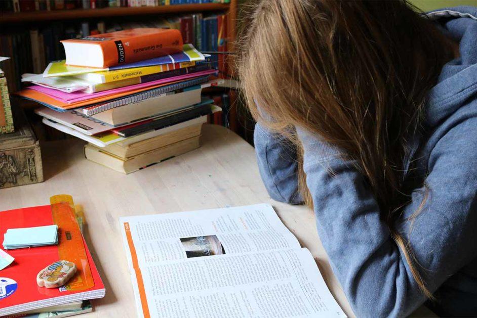 Kind vor Buch am Schreibtisch